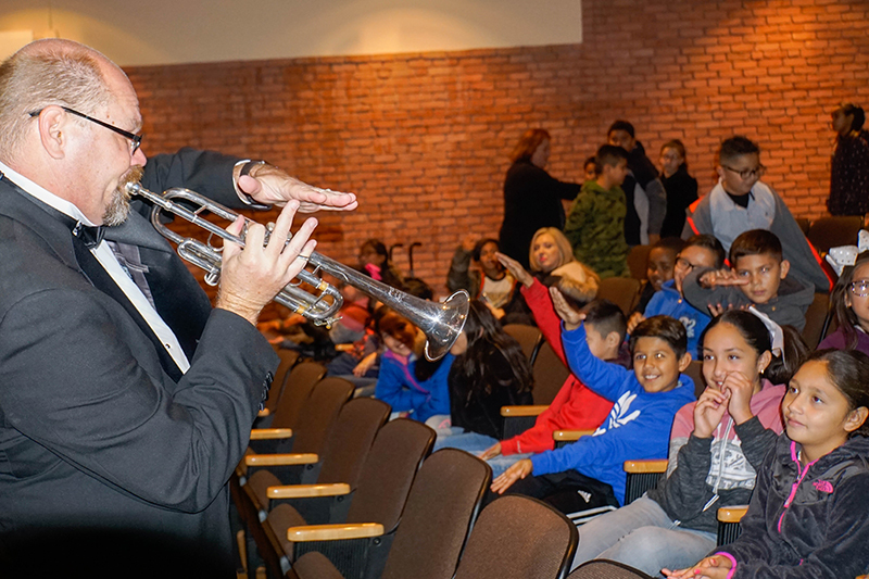 man in tuxedo blowing trumpet in front of seat of students