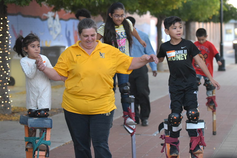 instructor helping two students walk on stilts
