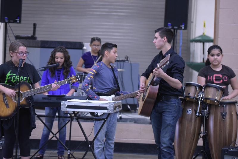 students standing up playing various instruments