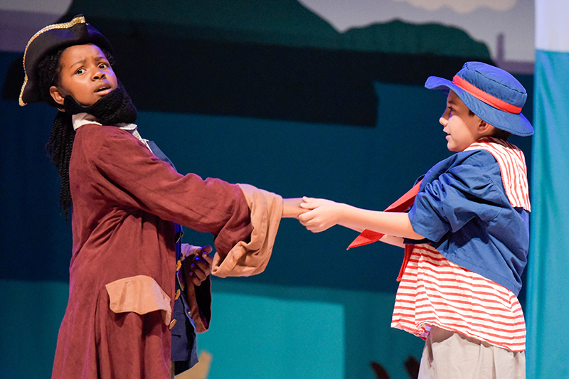 student in pirate costume and student in sailor costume on stage