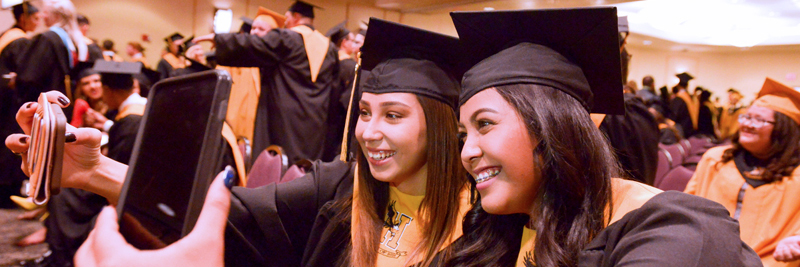 two girls in graduation gowns taking picture